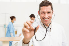 Doctor using stethoscope with colleagues and patient behind Royalty Free Stock Photos