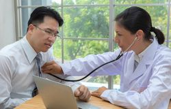 Doctor using the stethoscope listen to heartbeat of man patient royalty free stock image