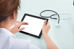Doctor using tablet computer at desk. Cropped image of female doctor using tablet computer at desk in clinic Stock Photography