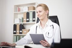 Doctor Using Tablet and Desktop Computer Together Royalty Free Stock Photos