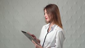 Doctor Using Tablet. Female doctor using tablet, intelligent and lovely woman with the gadget and stethoscope in the white background stock footage