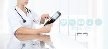 Doctor using tablet in medical office and icons Stock Photo