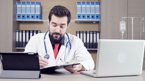 Doctor using a tablet pc to talk through video conference with his patient. Health care and medicine stock video footage