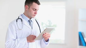 Doctor using a tablet tactile. In his office stock video footage