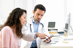 Doctor using tablet to inform patient. View of a Doctor using tablet to inform patient stock photo