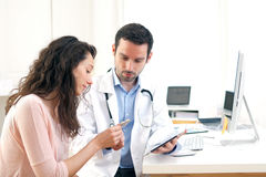 Doctor using tablet to inform patient. View of a Doctor using tablet to inform patient stock images