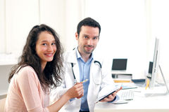 Doctor using tablet to inform patient. View of a Doctor using tablet to inform patient royalty free stock image