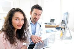 Doctor using tablet to inform patient. View of a Doctor using tablet to inform patient stock photography