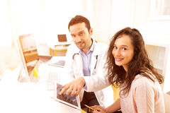 Doctor using tablet to inform patient. View of a Doctor using tablet to inform patient stock image