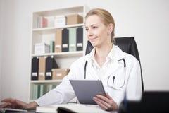 Doctor Using Tablet y equipo de escritorio junto Fotos de archivo libres de regalías