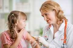 Doctor vaccinating frightened preschool child. Frightened child and doctor making vaccination Stock Photo