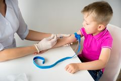 Doctor vaccinating a kid. Female doctor vaccinating a kid in clinic royalty free stock photo