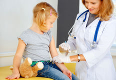 Doctor vaccinating small girl Stock Photo