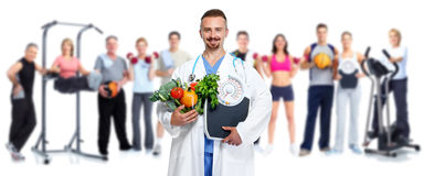 Doctor with vegetables and group of fitness people. Royalty Free Stock Photo