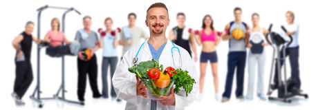 Doctor with vegetables and group of fitness people. Royalty Free Stock Images