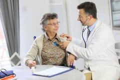 Doctor verifying the heart beat of an elderly woman Stock Photos
