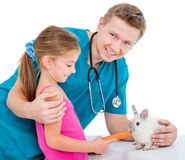 Doctor of veterenarii and little girl with rabbit. Veterenarii and a pretty  little girl feeding rabbit carrot Royalty Free Stock Photos