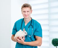 Doctor veterenarii with a rabbit. Young cute doctor veterenarii in the green uniform with a rabbit in his hands Royalty Free Stock Image