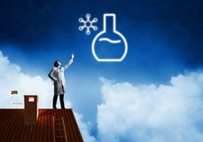 Doctor and vial symbol. Horizontal shot of young confident doctor in white medical uniform interracting with glowing vial symbol whie standing on brick roof with stock photography