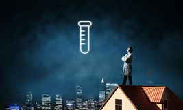 Doctor and vial symbol. Horizontal shot of young confident doctor in white medical uniform interracting with glowing vial symbol whie standing on brick roof with stock image
