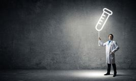 Doctor and vial symbol. Horizontal shot of young confident doctor in white medical uniform interracting with glowing vial symbol whie standing against dark gray stock photo