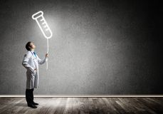 Doctor and vial symbol. Horizontal shot of young confident doctor in white medical uniform interracting with glowing vial symbol whie standing against dark gray royalty free stock images