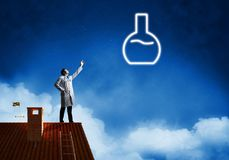 Doctor and vial symbol. Horizontal shot of young confident doctor in white medical uniform interracting with glowing vial symbol whie standing on brick roof with royalty free stock image
