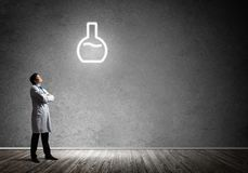 Doctor and vial symbol. Horizontal shot of young confident doctor in white medical uniform interracting with glowing vial symbol whie standing against dark gray stock image