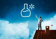 Doctor and vial symbol. Horizontal shot of young confident doctor in white medical uniform interracting with glowing vial symbol whie standing on brick roof with royalty free stock photo