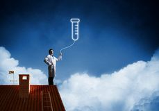 Doctor and vial symbol. Horizontal shot of young confident doctor in white medical uniform interracting with glowing vial symbol whie standing on brick roof with stock photos
