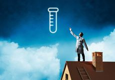 Doctor and vial symbol. Horizontal shot of young confident doctor in white medical uniform interracting with glowing vial symbol whie standing on brick roof with stock photo