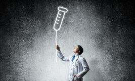 Doctor and vial symbol. Young confident doctor in white medical uniform interracting with glowing vial symbol whie standing against dark gray wall on background stock photos