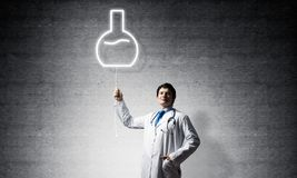 Doctor and vial symbol. Young confident doctor in white medical uniform interracting with glowing vial symbol whie standing against dark gray wall on background stock photo