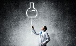Doctor and vial symbol. Young confident doctor in white medical uniform interracting with glowing vial symbol whie standing against dark gray wall on background royalty free stock photo