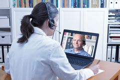 Doctor video call male patient. Doctor or pharmacist sitting at the desk of her office with headset and laptop, taking notes during a video call with an male Stock Image