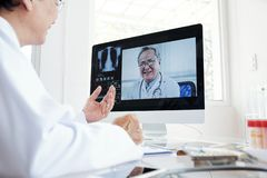 Doctor video calling his coworker stock images