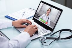 Doctor Video Conferencing On Laptop. With His Female Colleague royalty free stock images