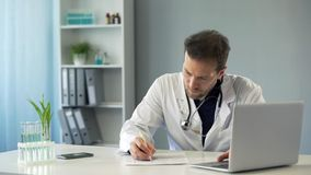 Doctor viewing test results on laptop and writing down medical records, medicine royalty free stock images