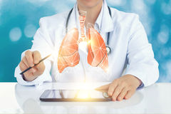 The doctor on the virtual screen shows a model of a human lung. stock image