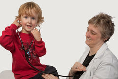 Doctor visit. Young caucasian boy and a short hair woman in uniform holding a stethoscope on his ear listening to doctor heart beat Stock Photo