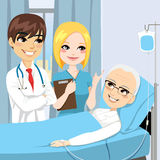Doctor Visit Senior Patient. Doctor and nurse visit a senior old man patient lying down on hospital bed receiving intravenous chemotherapy cancer treatment Royalty Free Stock Photo
