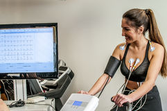 Doctor visit. S a young girl with electrocardiogram during cyclette Stock Photos