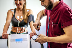Doctor visit. S a young girl with electrocardiogram during cyclette Stock Photo
