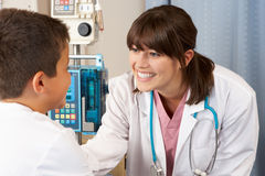 Doctor Visiting Child Patient On Ward Stock Photo