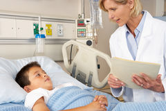 Doctor Visiting Child Patient On Ward Royalty Free Stock Photos