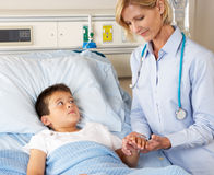 Doctor Visiting Child Patient On Ward Stock Images