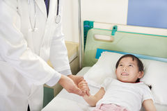 Doctor Visiting Child Patient On Ward Royalty Free Stock Image