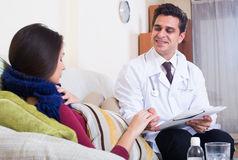 Doctor visiting female patient suffering of cold at home Royalty Free Stock Image