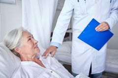 Doctor visiting happy senior woman at hospital Stock Image