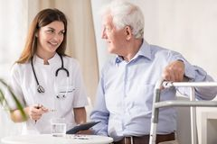 Doctor visiting patient at home Stock Image